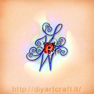 Illustrazione a colori maiuscole nascoste JLW con riccioli decorativi e coccinella porta fortuna.